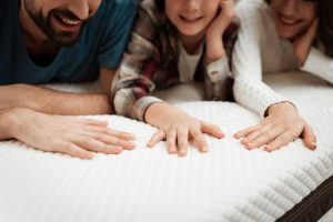 Young couple together with their young son test material of mattress for a touch.