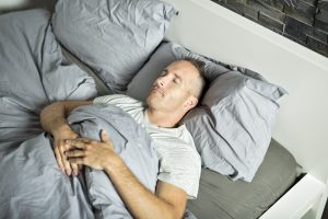 Portrait of a young man from above sleeping in be