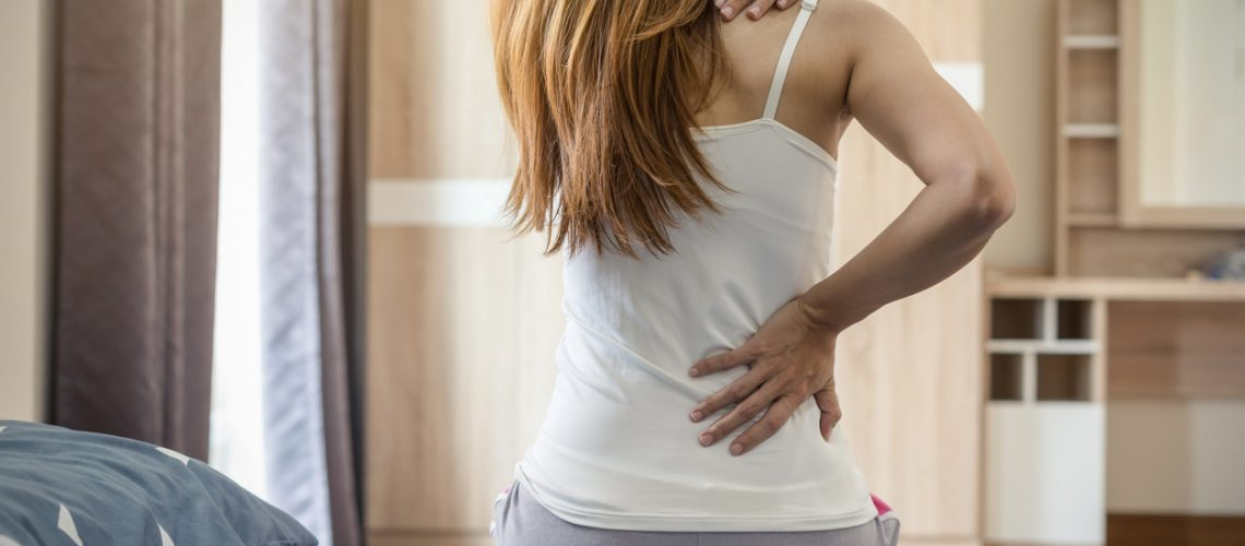 Woman suffering from back ache on the bed