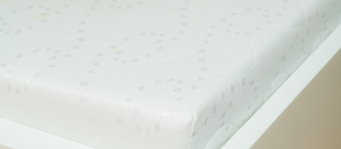 Close up of memory foam mattress on the bed frame at sleeping room. Comfort, choosing mattress